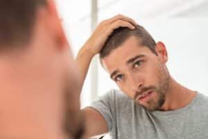 Man examining his hair for hair loss in a mirror.