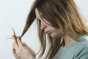 Woman with brown hair looking at her split ends.
